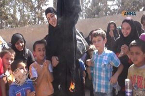 صور: امرأة سورية تحرق نقابها احتفالا بتحرير مدينتها من قبضة داعش