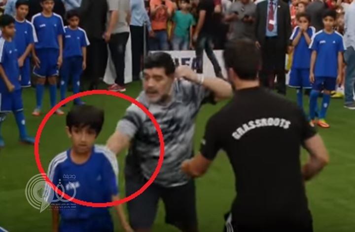 """بالفيديو.. طفل يحرج """"مارادونا"""" ويسقطه أرضا خلال استعراضه بالكرة في البحرين"""