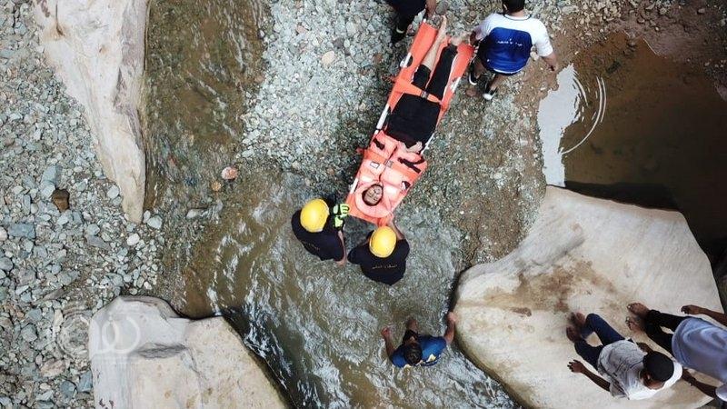 """شاهد بالفيديو والصور.. """"مدني جازان"""" في مهمة صعبة خلف الصخور لإنقاذ شاب سقط بـ""""وادي لجب"""""""
