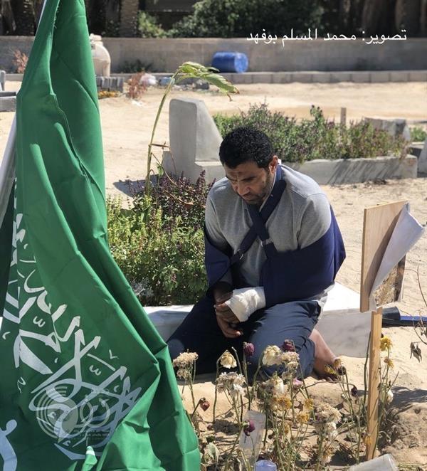 """صورة مؤثرة لجندي مصاب يزور """"قبر"""" زميله الذي استشهد بالحد الجنوبي"""