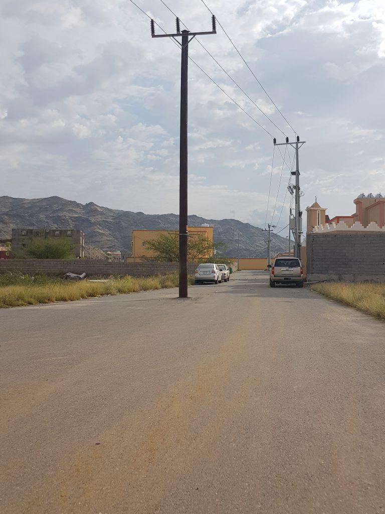 """بالصور : عمود كهرباء """"ضغط عالي"""" يتوسط الطريق بأحد أحياء """"مركز الحقو"""" ويُنذر بكارثة"""
