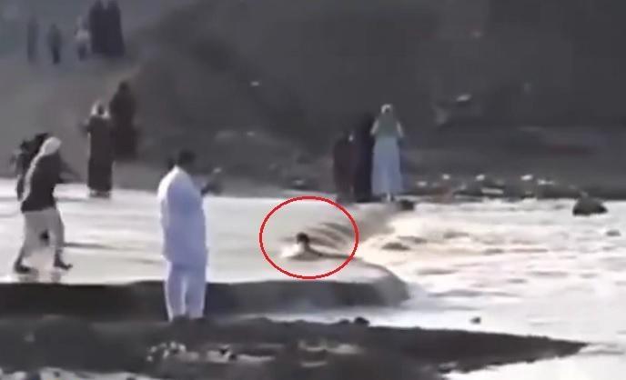 """شاهد : ردة فعل مثيرة وبطولية لـ""""أب"""" رأى طفله يسقط وسط مياه السيل"""